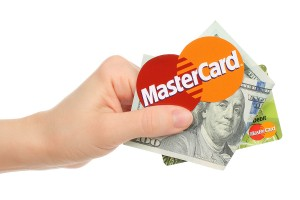 Kiev, Ukraine - January 15, 2016: Hand holds Mastercard logo printed on paper with money and credit card on white background